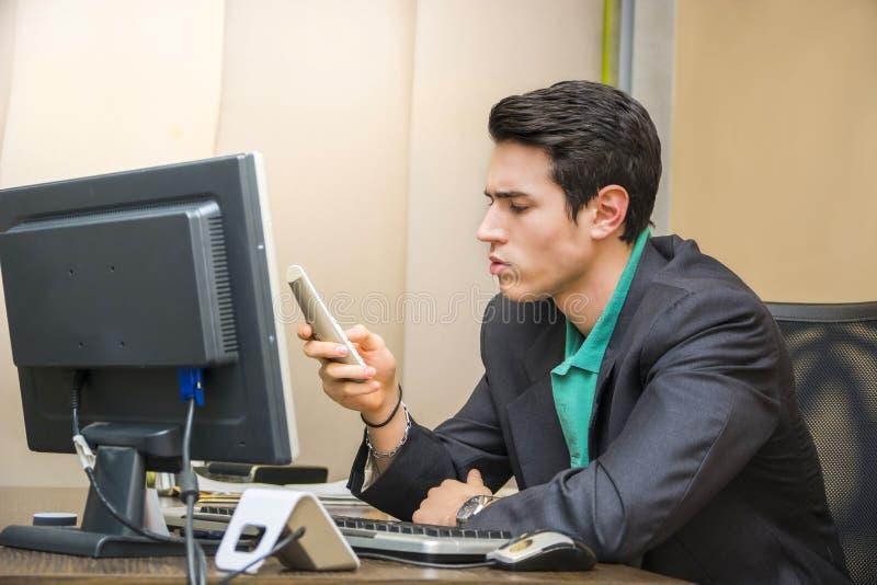 Knappe jonge zakenman bij bureau op telefoon stock afbeelding