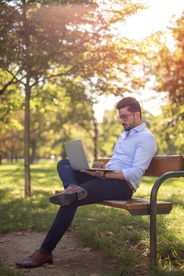 Knappe jonge zakenman die aan zijn laptop in het park werken royalty-vrije stock fotografie