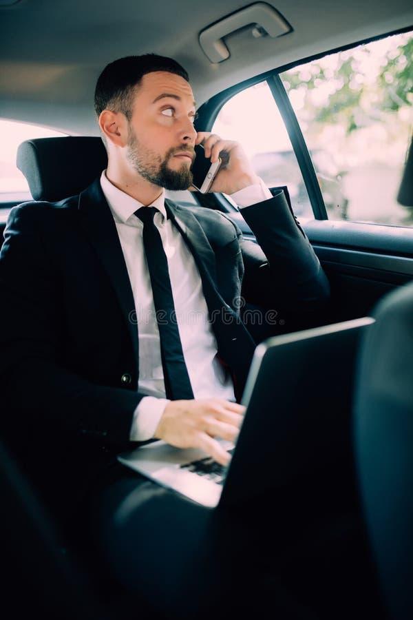 Knappe jonge zakenman die aan zijn laptop werken en op de telefoon spreken terwijl het zitten in de auto stock foto