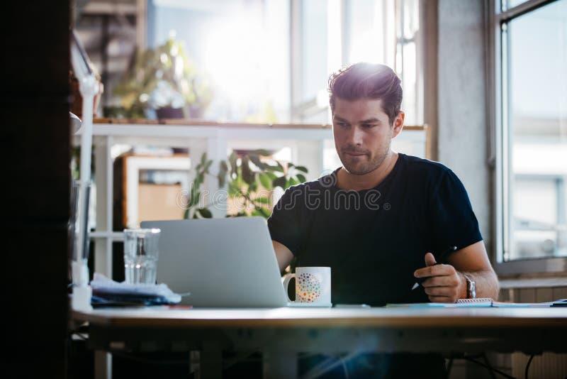 Knappe jonge zakenman die bij zijn bureau werken stock foto's