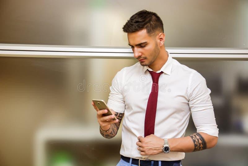 Knappe jonge zakenman die celtelefoon met behulp van royalty-vrije stock fotografie