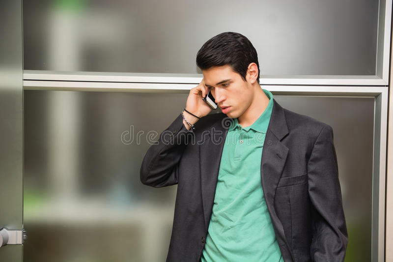 Knappe jonge zakenman die op celtelefoon spreken royalty-vrije stock afbeelding