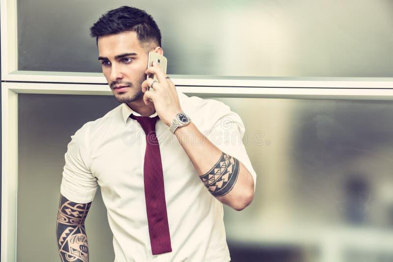 Knappe jonge zakenman die op celtelefoon spreken royalty-vrije stock fotografie
