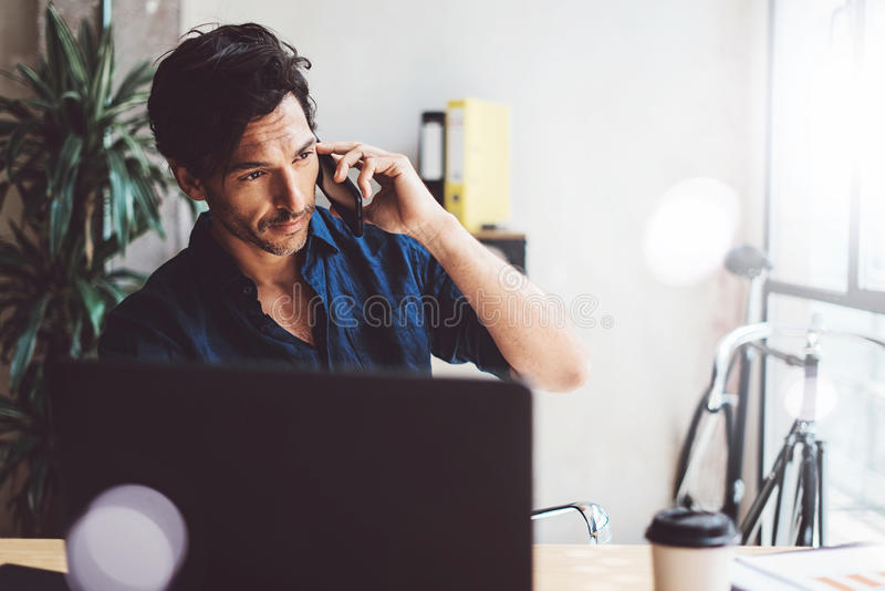 Knappe jonge zakenman die op zonnige het werkplaats aan laptop werken Glimlachende Mens die mobiel telefoongesprek maken terwijl stock afbeelding