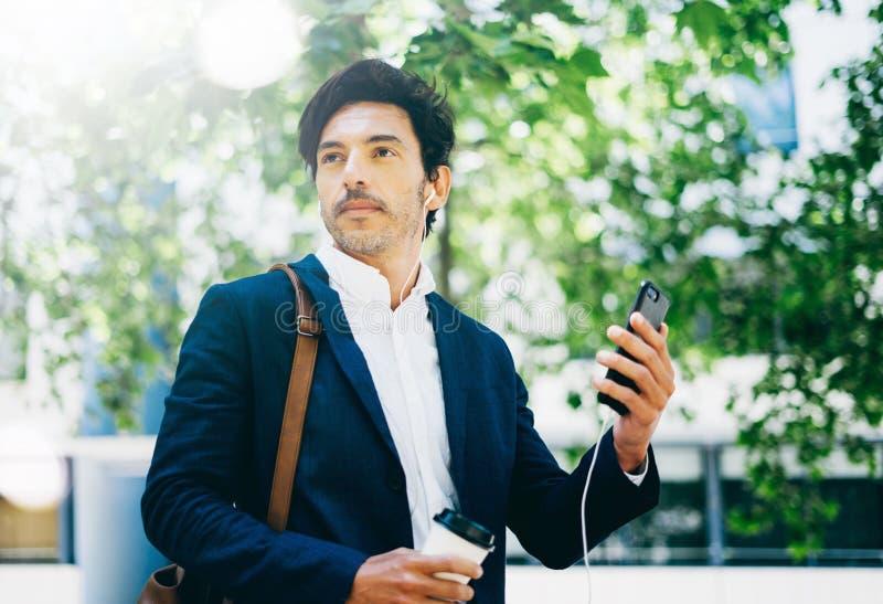 Knappe jonge zakenman die smartphone voor het listining van muziek gebruiken terwijl het lopen in stadspark Horizontale, vage ach stock foto