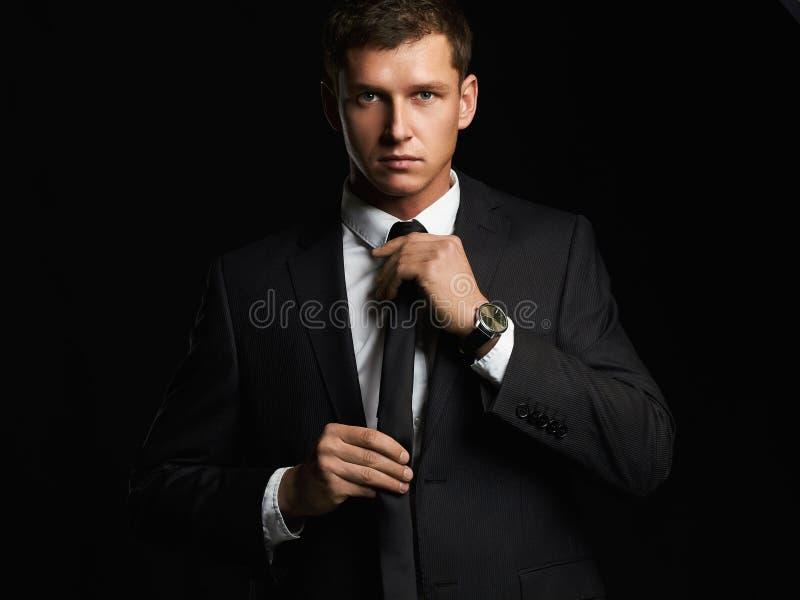 Knappe jonge zakenman die zijn band aanpast Jonge mens in kostuum stock afbeeldingen