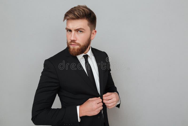 Knappe jonge zakenman in kostuum die en zich camera bevinden bekijken stock afbeeldingen