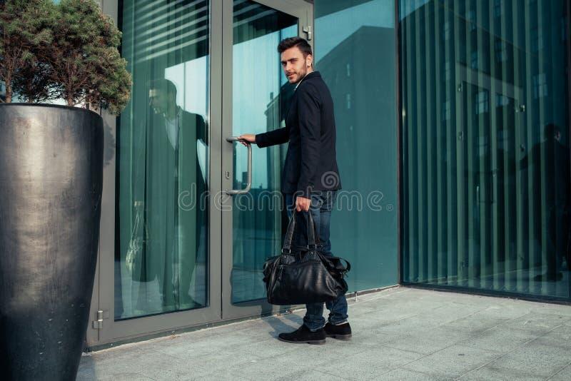 Knappe jonge zakenman met een baard en in een pak die zich op de straat bevinden royalty-vrije stock foto