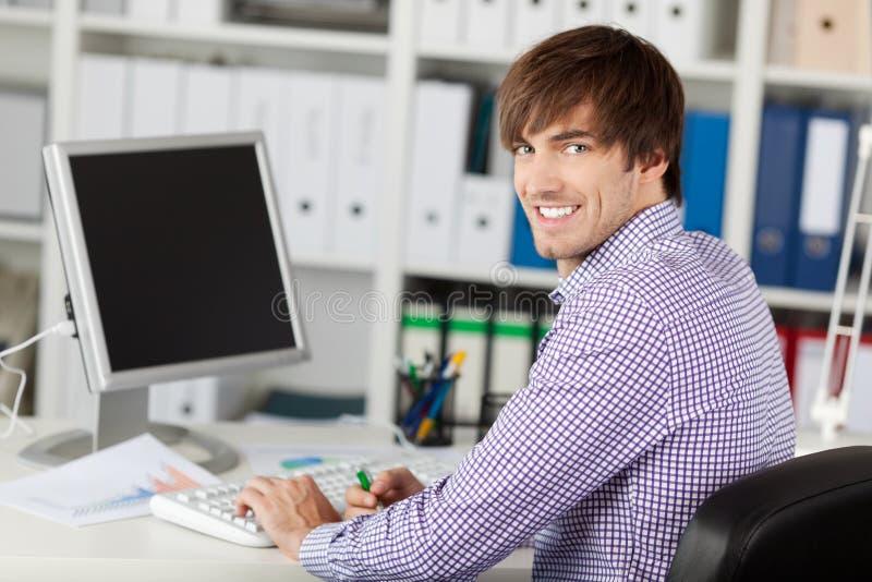 Knappe Jonge Zakenman Smiling At Desk stock afbeelding