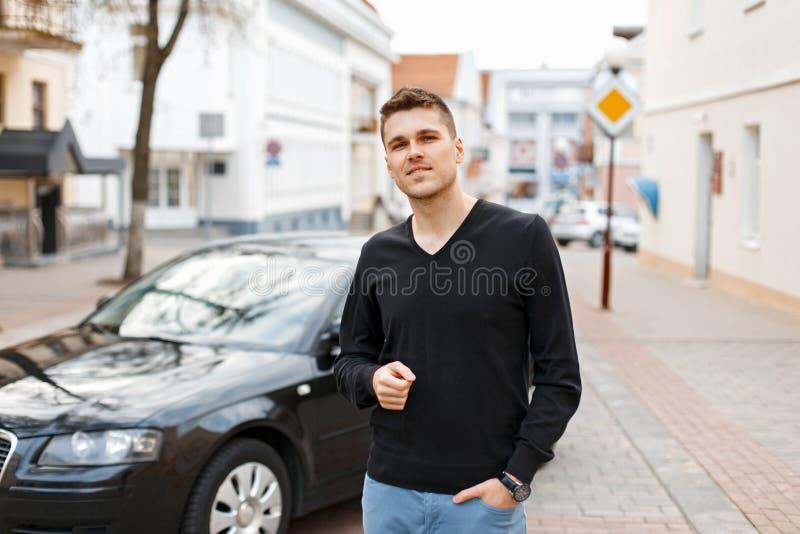 Knappe jonge zakenmanmens dichtbij een zwarte auto op de straat royalty-vrije stock fotografie