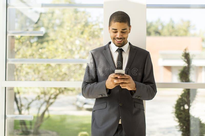 Knappe jonge zwarte mens met mobiele telefoon stock afbeeldingen