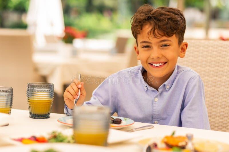 Knappe jongen die terwijl het genieten van van ontbijt glimlachen stock afbeelding