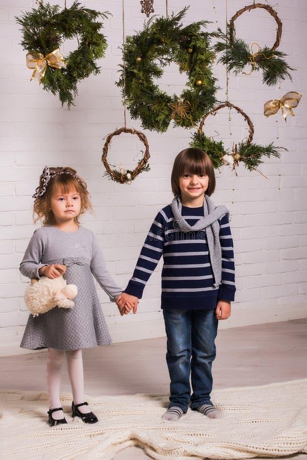Knappe jongen en leuk klein meisje op Kerstmisachtergrond stock foto