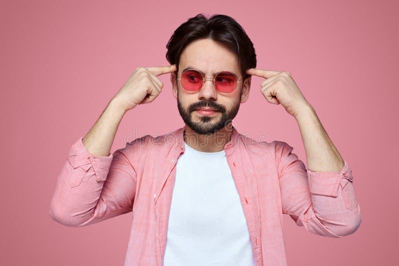 Knappe jongen modieuze uitrusting dragen en zonnebril die weg met nadenkende uitdrukking kijken, die wijsvingers op zijn hoofd ho stock afbeelding