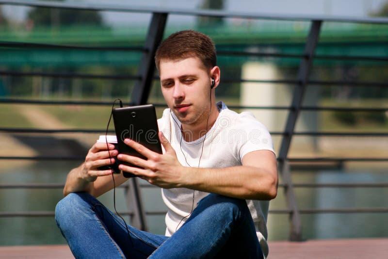 Knappe jongen tablet en hoofdtelefoons met behulp van, het drinken koffie om te gaan, mensenzitting op gras en het genieten die v royalty-vrije stock foto's