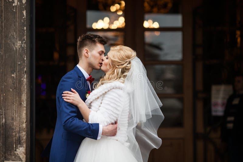 Knappe jonggehuwdebruidegom die gelukkige bruid buiten kerk daarna kussen stock foto