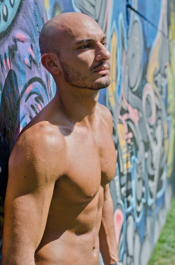 Knappe kale jonge mens shirtless op graffitimuur stock afbeelding