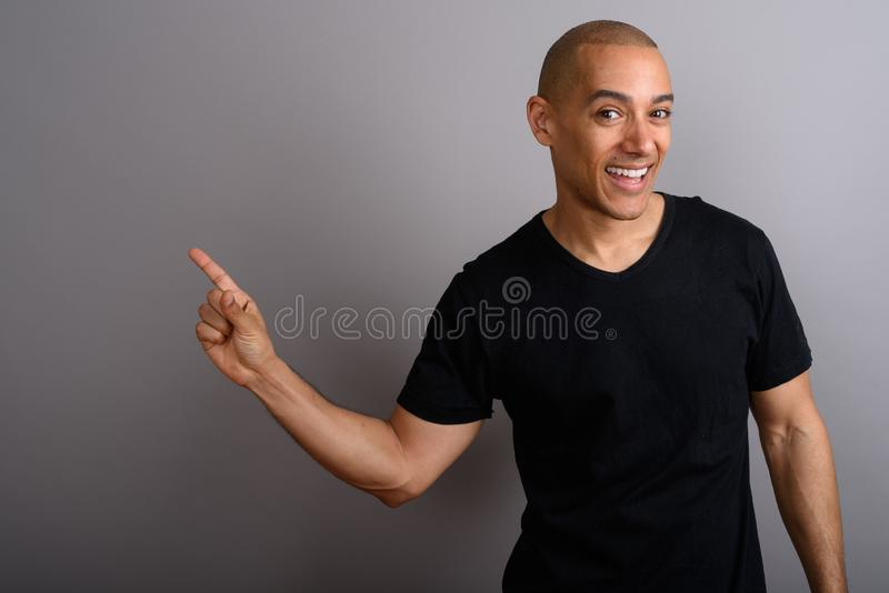 Knappe kale mens die en exemplaarruimte met het richten van vinger glimlachen tonen stock foto's