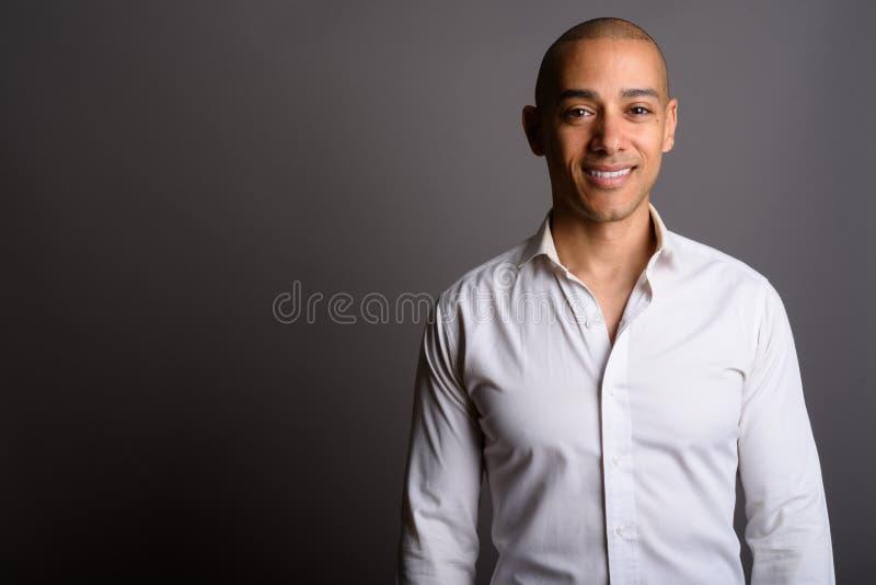 Knappe kale zakenman die tegen grijze achtergrond glimlachen royalty-vrije stock foto