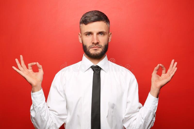 Knappe kalme zakenman op kleurenachtergrond stock afbeelding