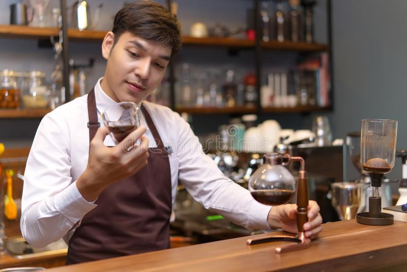 Knappe Kaukasische barista die een kop gietende koffie met Syp houden stock foto's