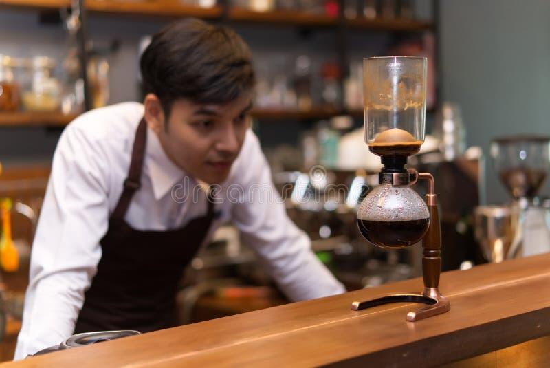 Knappe Kaukasische barista Looking bij geëindigd brouwt sifon c royalty-vrije stock afbeelding