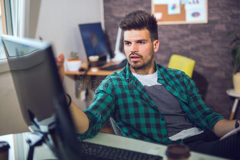 Knappe Kaukasische mens bij het werkbureau stock afbeeldingen