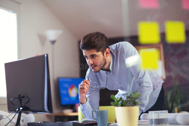 Knappe Kaukasische mens bij het werkbureau die vlakke het schermcomputer onder ogen zien stock afbeelding
