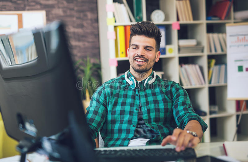 Knappe Kaukasische mens bij het werkbureau die vlakke het schermcomputer onder ogen zien royalty-vrije stock foto