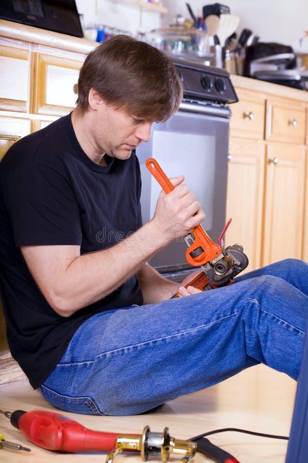 Knappe Kaukasische mens die in keuken werken stock afbeelding