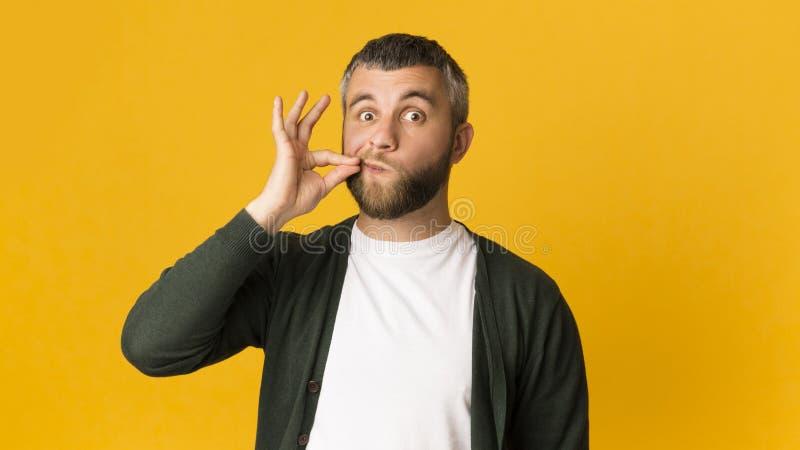 Knappe Kaukasische mens die zijn mond met gebaar snellen stock fotografie