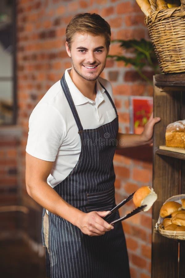 Knappe kelner die een broodje opnemen stock fotografie