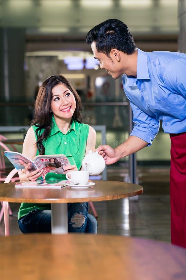 Knappe kelner die met een mooie vrouw flirten terwijl het dienen van koffie royalty-vrije stock fotografie
