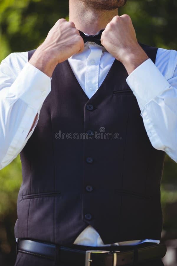 Knappe kelner die zijn vlinderdas weer vastmaken royalty-vrije stock afbeelding