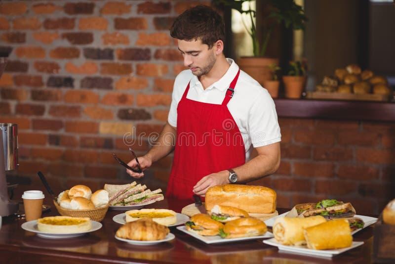 Knappe kelner ongeveer om een broodje te plukken royalty-vrije stock fotografie