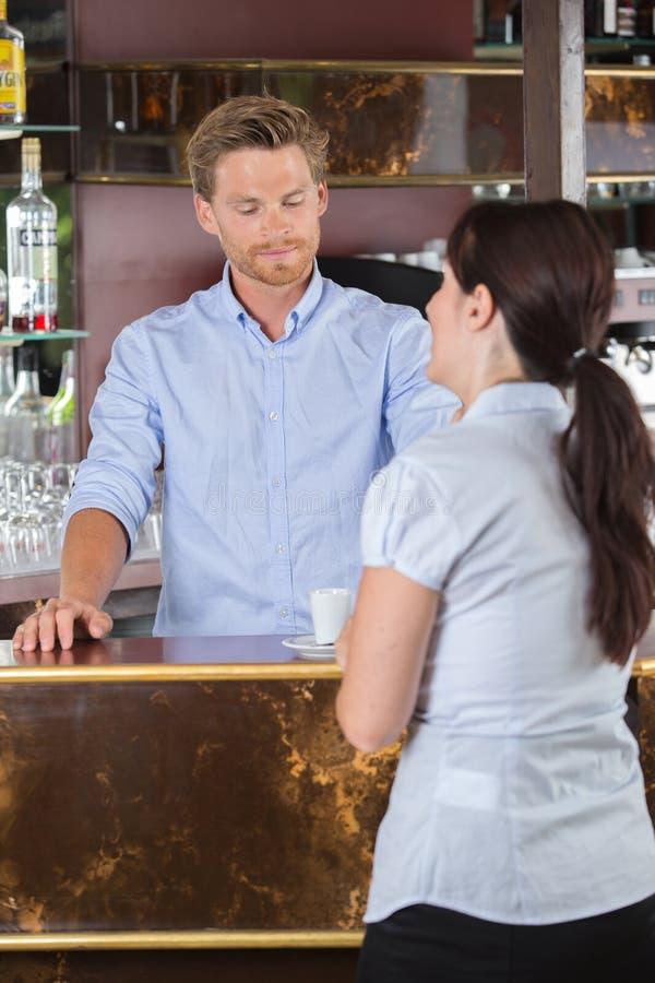 Knappe kelners dienende koffie aan klant bij koffiewinkel royalty-vrije stock fotografie