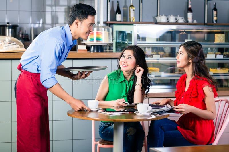 Knappe kelners dienende koffie bij de lijst van twee mooie vrouwen stock foto's