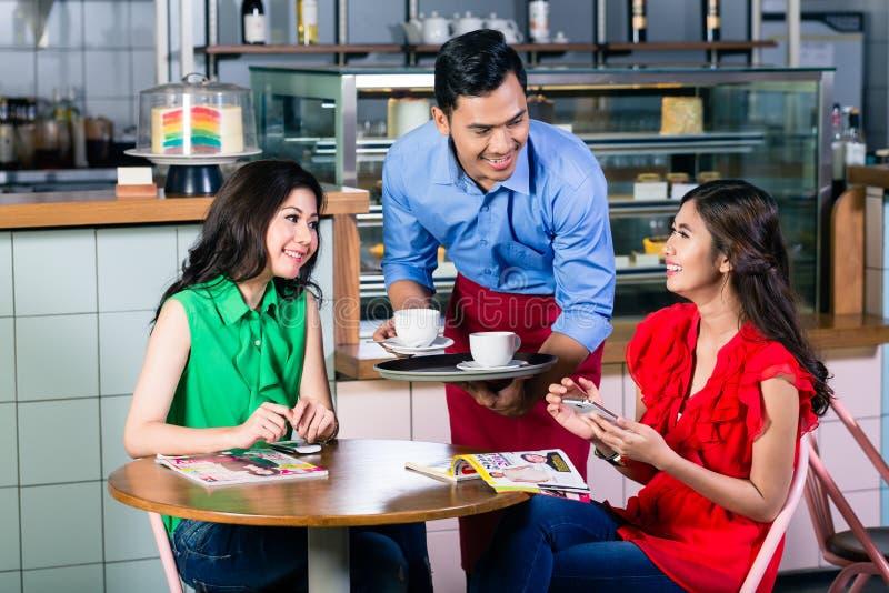 Knappe kelners dienende koffie bij de lijst van twee mooie vrouwen royalty-vrije stock afbeeldingen