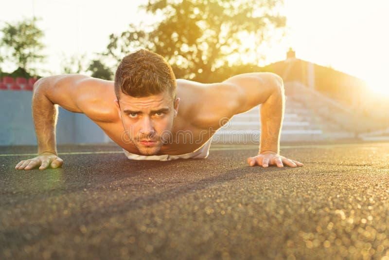Knappe kerel die opdrukoefeningen in openlucht op een zonnige de zomerdag doen stock afbeeldingen