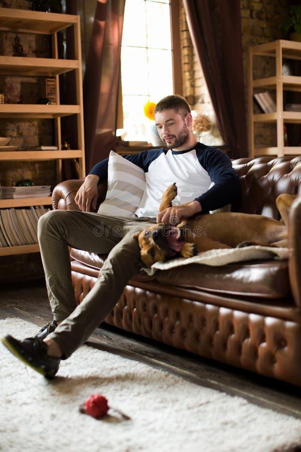 Knappe kerel die thuis met zijn hond spelen royalty-vrije stock afbeelding