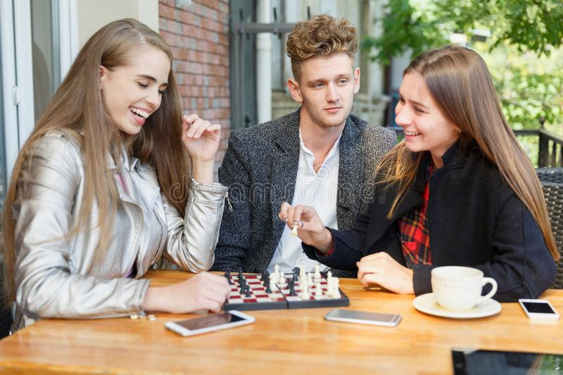 Knappe kerel en slimme meisjesvrienden die schaak op een koffieachtergrond spelen Het concept van intelligentiespelen royalty-vrije stock foto