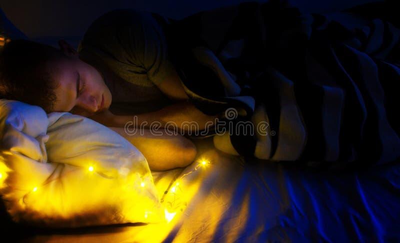 Knappe kerel hipster, slapend in haar wit bed, in de nacht, droom over het gelukkige leven royalty-vrije stock foto's