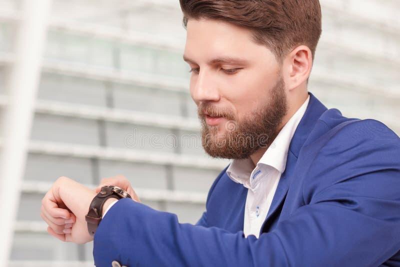 Knappe kerel met baard die tijd controleren stock afbeelding