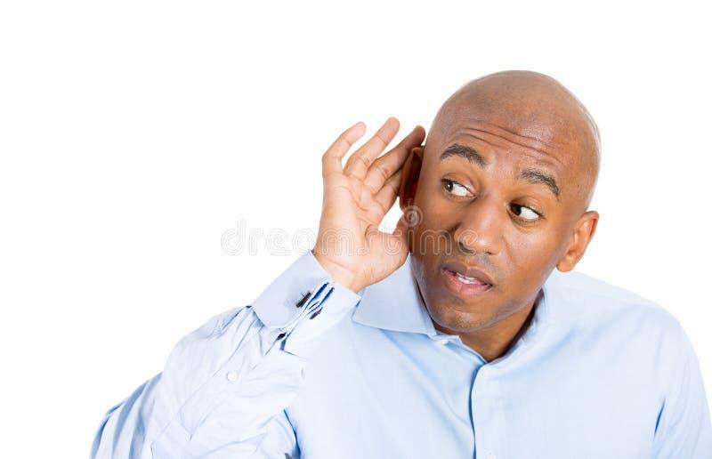 Knappe kerel met blauw overhemd die in het geheim binnen op een gesprek proberen te luisteren en geschokt bij wat hij hoort royalty-vrije stock afbeelding