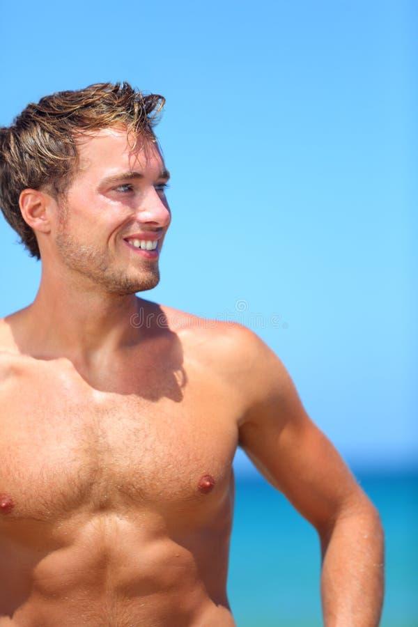 Knappe knappe mens bij strand gelukkig glimlachen royalty-vrije stock fotografie