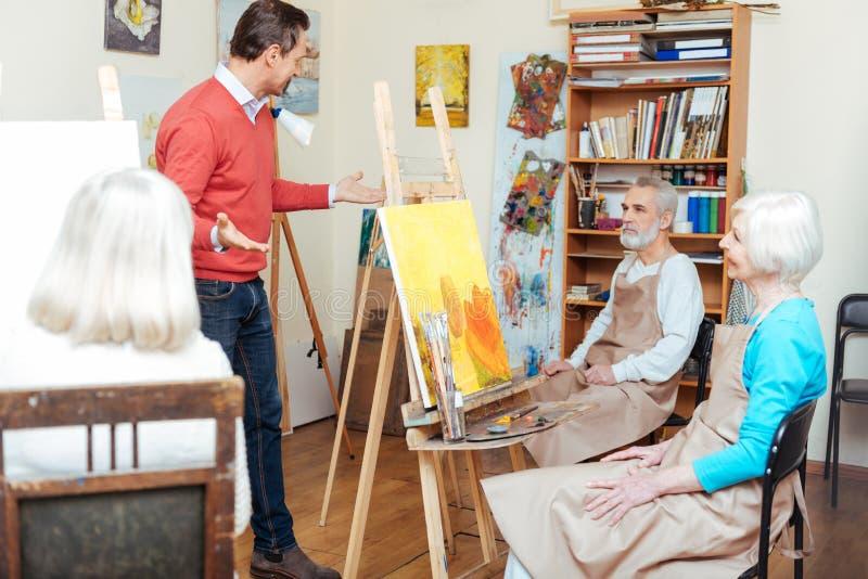 Knappe kunstenaar die in het schilderen van school spreken stock foto's