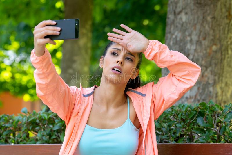 Knappe Latijnse agent die het geschikte en gezonde vermoeide en uitgeputte nemen selfie in een modern groen park kijken stock afbeelding