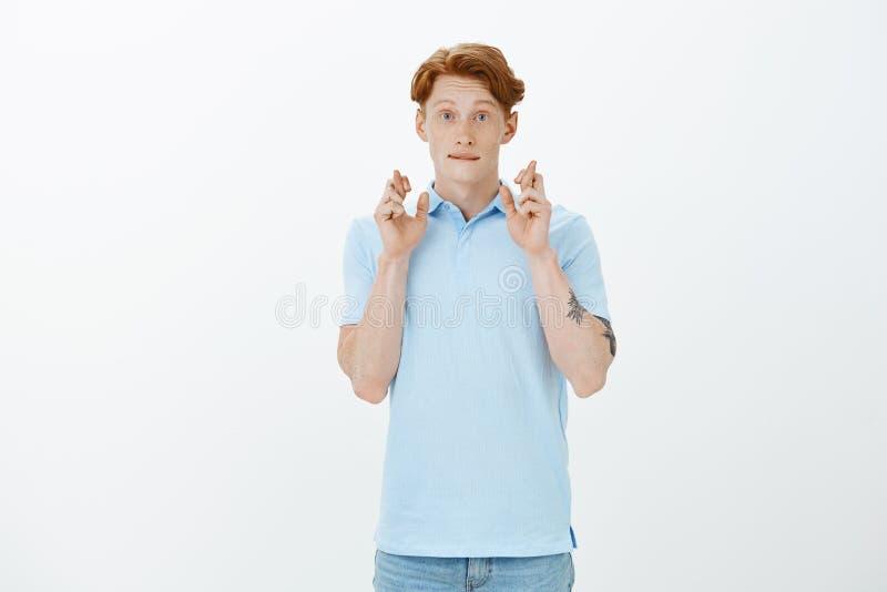 Knappe leuke vriend met gemberhaar die gekruiste vingers opheffen en met vriendelijke en tedere uitdrukking glimlachen stock fotografie
