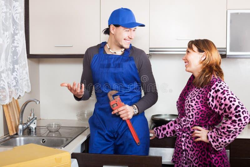 Knappe loodgieter die met huisvrouw spreken stock fotografie