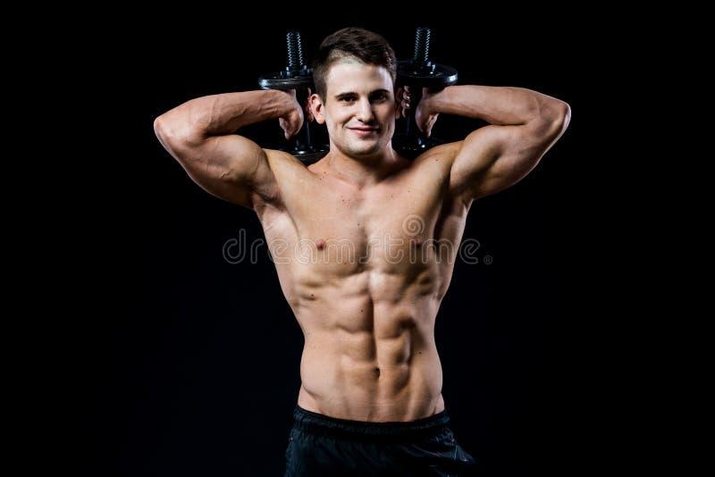 Knappe machts atletische mens die omhoog pompend spieren met domoren in een gymnastiek opleiden Barbells achter het hoofd Geschik stock afbeelding